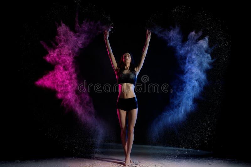 Posição atrativa da mulher no fumo colorido com mãos acima imagens de stock