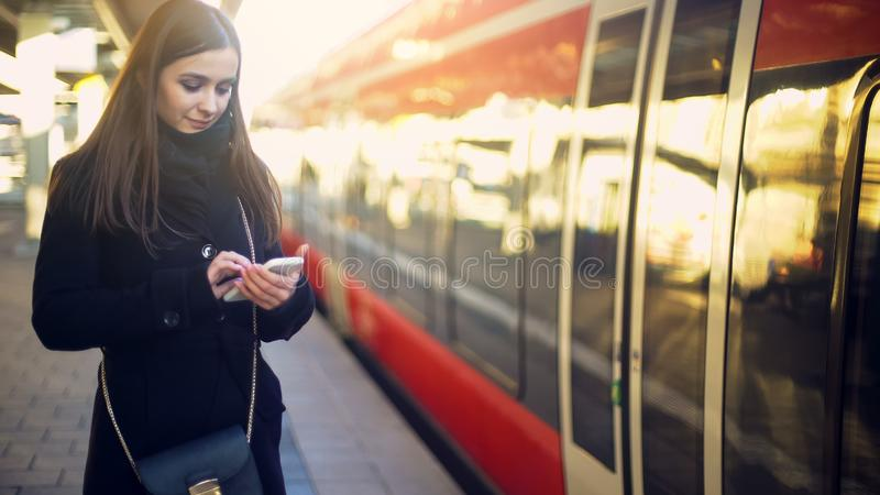 Posição atrativa da senhora perto do trem e datilografia no smartphone, bilhetes em linha fotos de stock royalty free