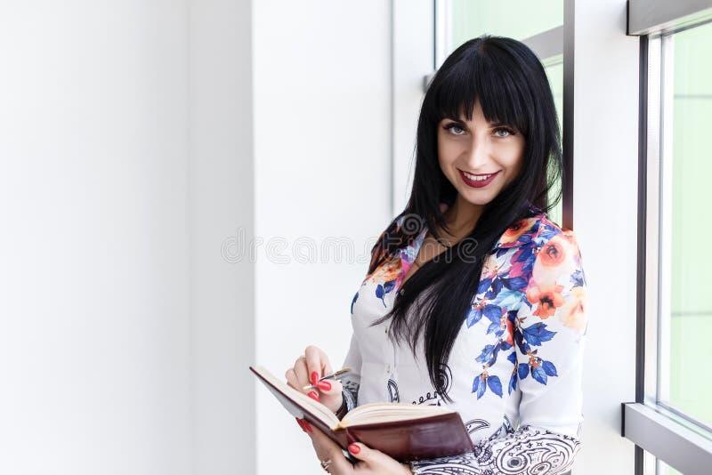 Posição atrativa nova da mulher de negócios perto da janela, escrevendo em um caderno, olhando o sorriso da câmera fotos de stock