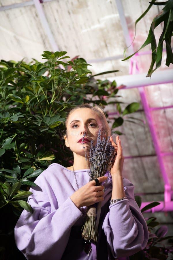 Posição bonita agradável da mulher com flores bonitas fotografia de stock royalty free