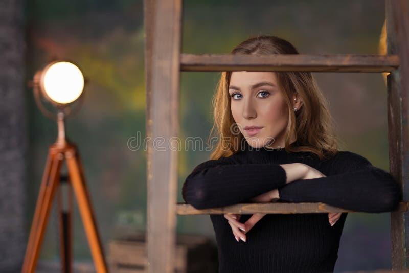 Posição bonita bonita da jovem mulher, inclinando-se na escada Mim imagens de stock royalty free
