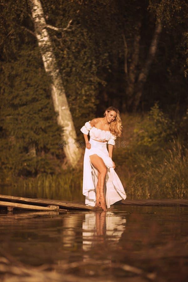 Posição bonita da jovem mulher pelo lago que mostra seus pés 'sexy' fotografia de stock royalty free