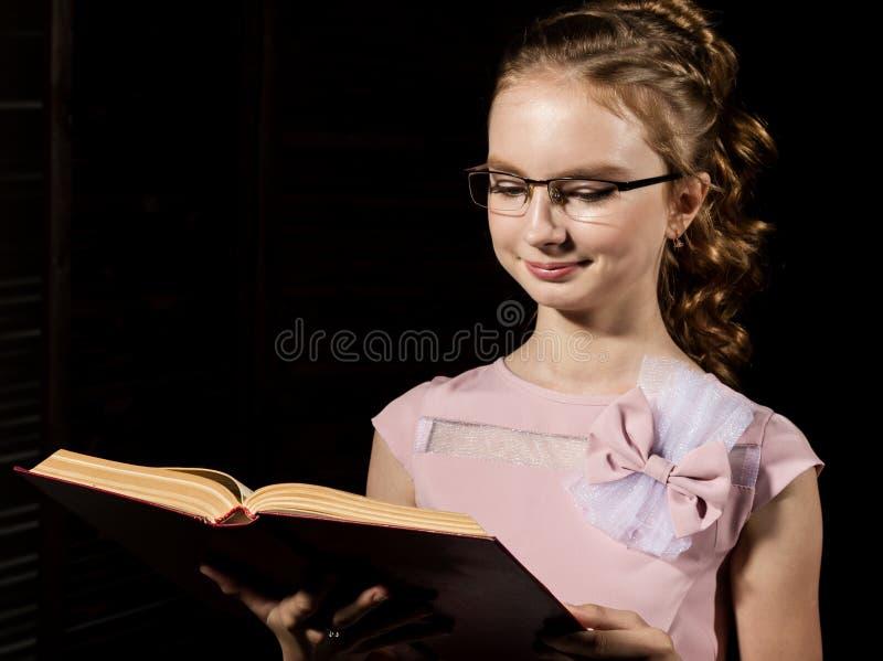 A posição bonita da menina e lê o livro sobre o fundo escuro imagens de stock royalty free
