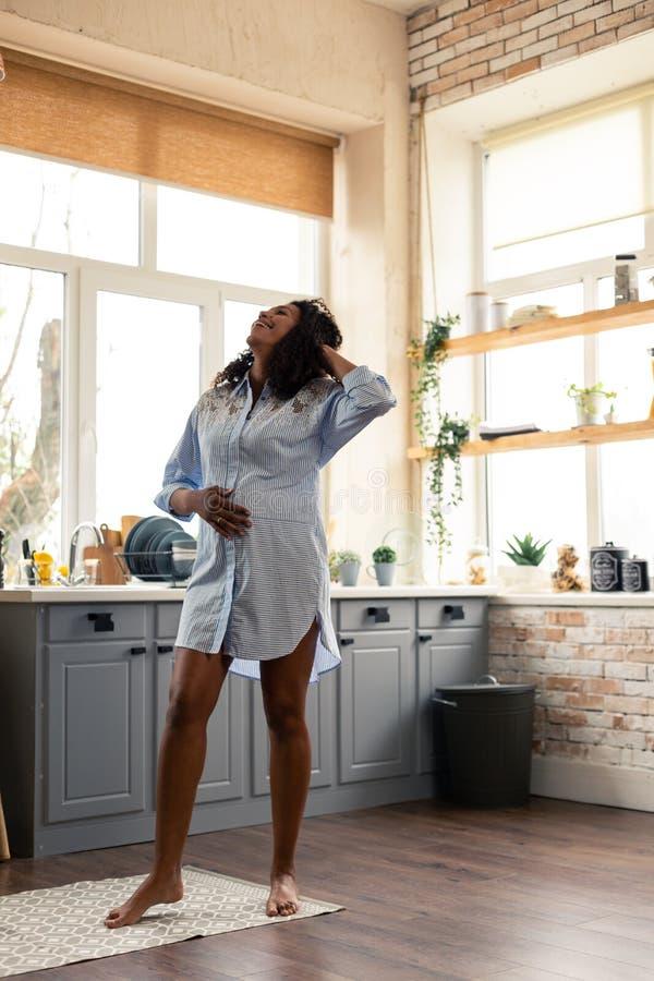Posição bonita da mulher gravida em sua cozinha imagens de stock