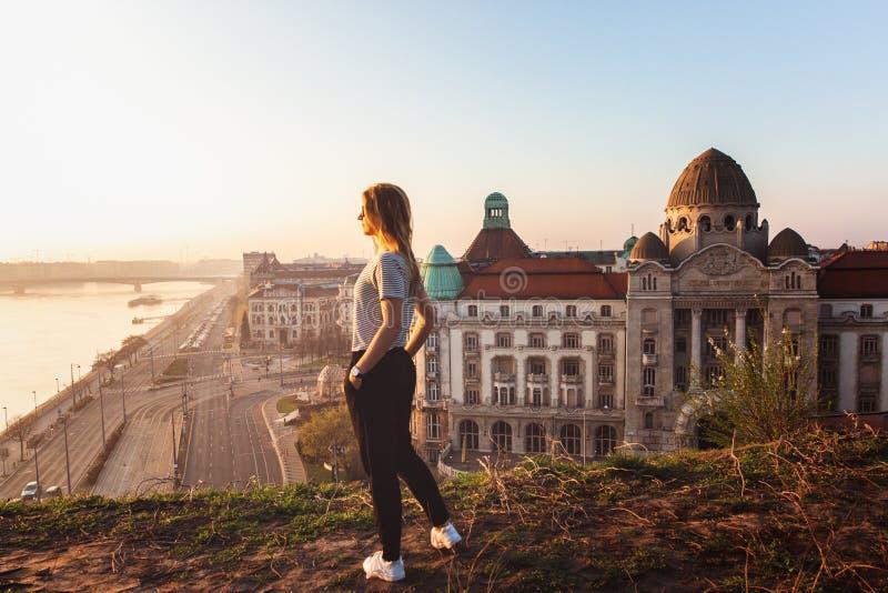Posição bonita da mulher oposto à fachada famosa e entrada ao hotel Gellert em bancos de Danúbio em Budapest, Hungria fotos de stock royalty free