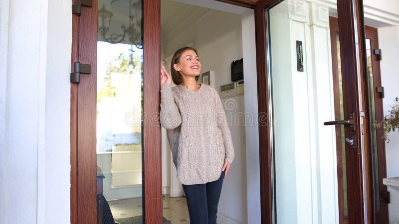 Posição bonita da mulher pela casa e sorriso, marido de espera do trabalho imagem de stock royalty free