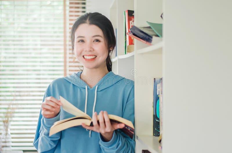Posição bonita de sorriso da moça na biblioteca em casa com livros, mulher que lê um livro imagens de stock