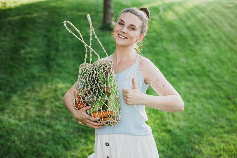 Posição bonita nova da mulher com o saco de compras zero ecológico do desperdício com vegetais imagens de stock