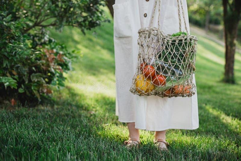 Posição bonita nova da mulher com o saco de compras zero ecológico do desperdício com vegetais fotografia de stock royalty free