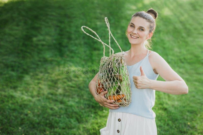 Posição bonita nova da mulher com o saco de compras zero ecológico do desperdício com vegetais fotografia de stock
