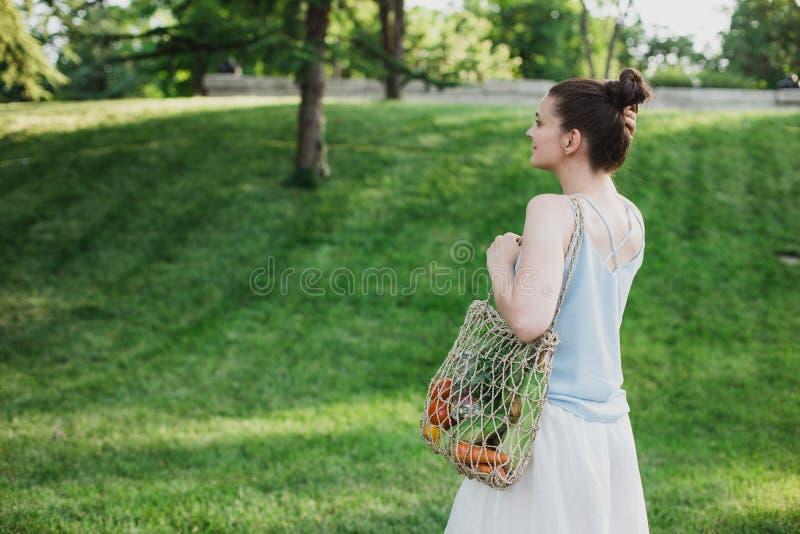 Posição bonita nova da mulher com o saco de compras zero ecológico do desperdício com vegetais fotos de stock royalty free