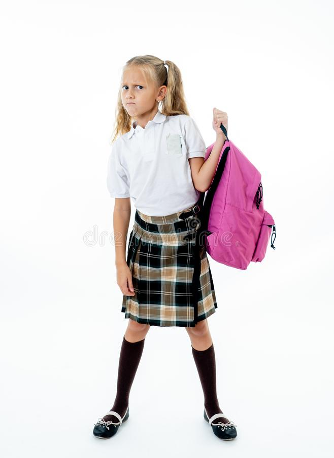 Posição bonito cansado e triste nova da menina da escola com um saco de escola pesado grande nela para trás em um fundo branco do fotos de stock