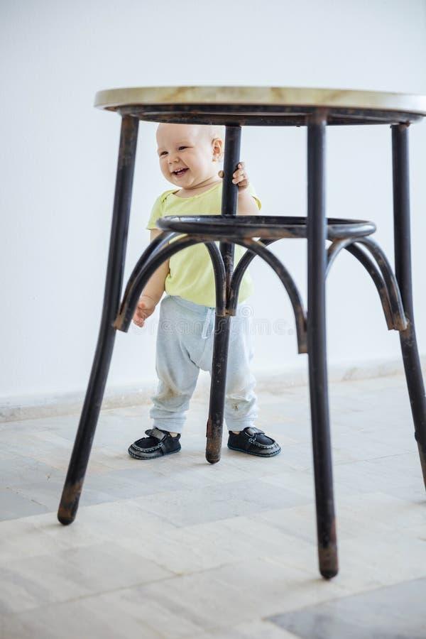 Posição bonito do bebê ao prender o pé do tamborete e do riso fotografia de stock