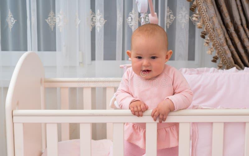 Posição bonito do bebê na ucha na cena cor-de-rosa do quarto imagem de stock royalty free