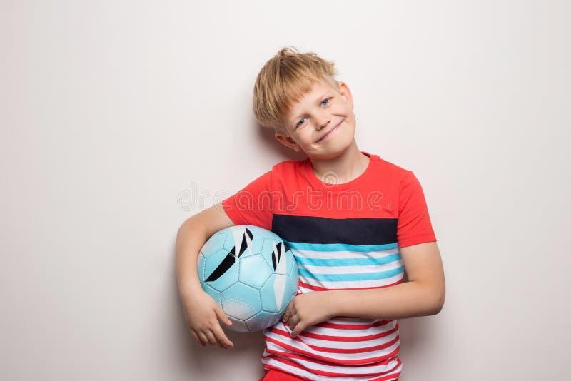 Posição bonito do rapaz pequeno com bola de futebol e vista da câmera Isolado no branco Retrato do est?dio fotos de stock royalty free