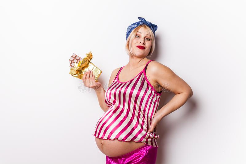 Posição bonito feliz da mulher gravida isolada sobre o fundo branco que come o chocolate imagem de stock