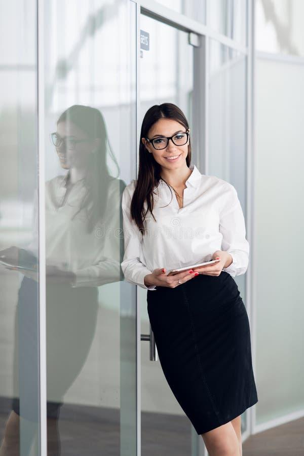 Posição branca vestindo da blusa da mulher de negócio no salão do escritório com tablet pc e sorriso foto de stock royalty free