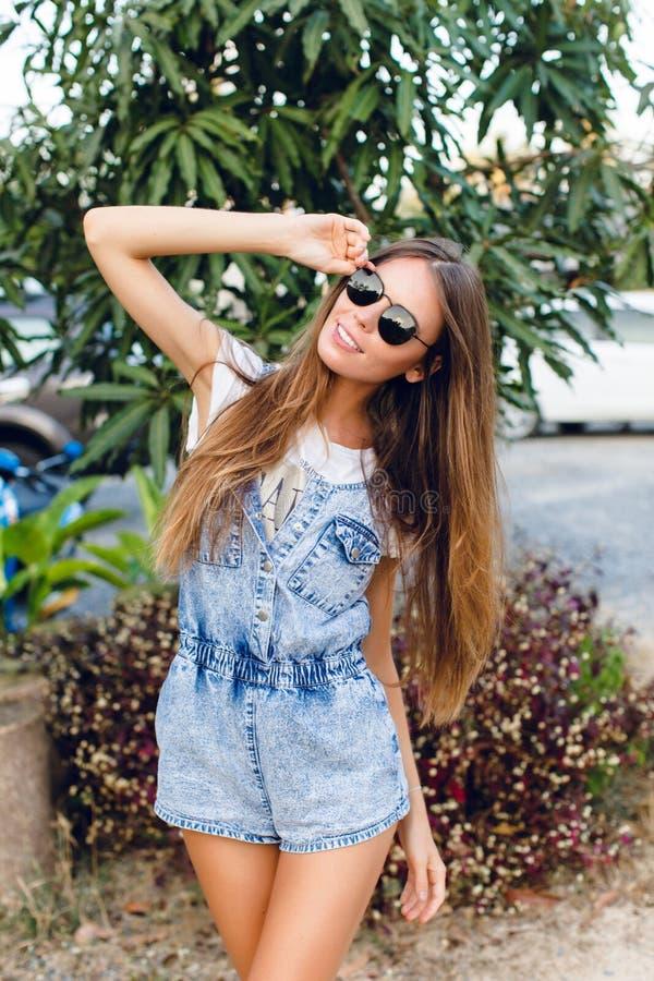 Posição bronzeada magro bonito da menina perto da árvore Veste o t-shirt branco, o short da sarja de Nimes e óculos de sol pretos fotografia de stock royalty free