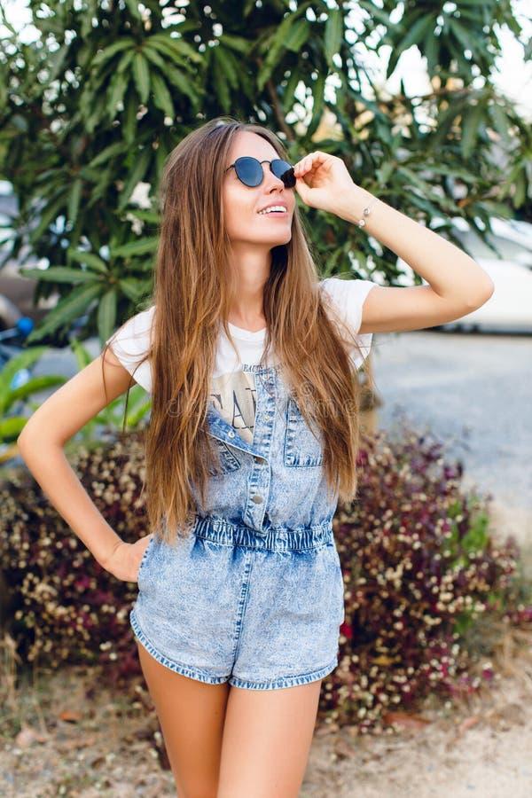Posição bronzeada magro bonito da menina perto da árvore Veste o t-shirt branco, o short da sarja de Nimes e óculos de sol pretos imagens de stock royalty free