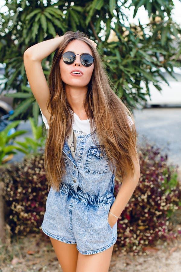 Posição bronzeada magro bonito da menina perto da árvore Veste o t-shirt branco, o short da sarja de Nimes e óculos de sol pretos foto de stock royalty free