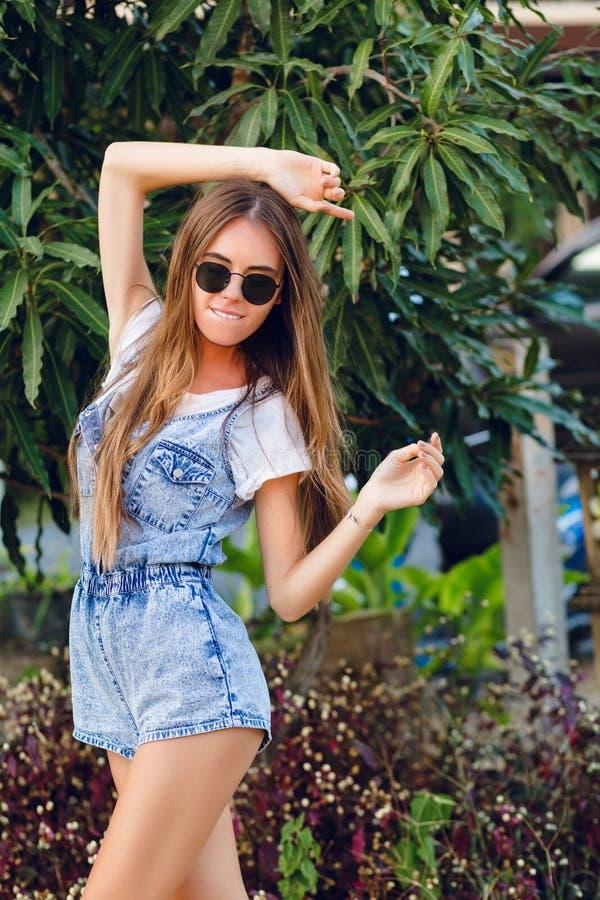 Posição bronzeada magro bonito da menina perto da árvore Veste o t-shirt branco, o short da sarja de Nimes e óculos de sol pretos imagens de stock
