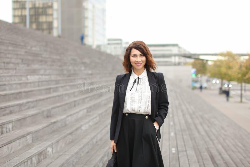 Posição businesslady europeia em escadas fora no fundo alto das construções foto de stock