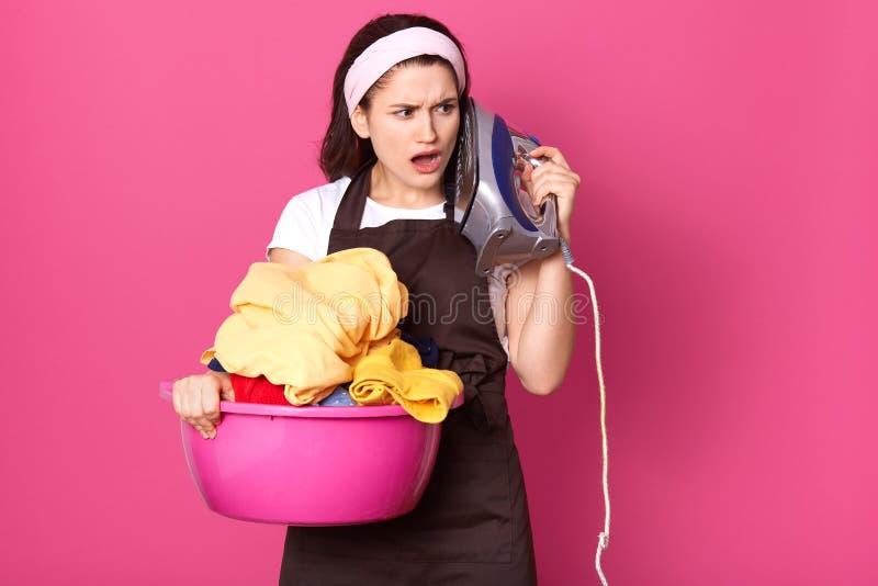 Posição cansado da dona de casa Impressed isolada sobre o fundo cor-de-rosa no estúdio, guardando a bacia com a roupa e o ferro,  fotografia de stock royalty free