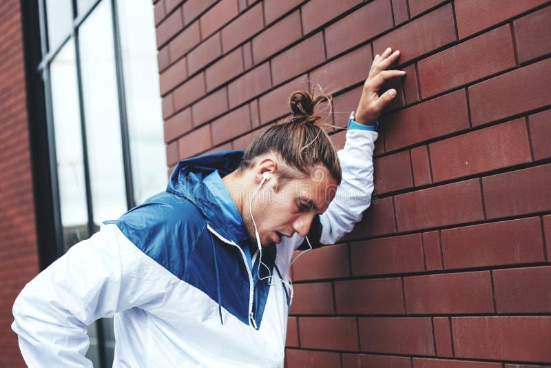 Posição cansado do atleta na rua perto da parede e do descanso de tijolo, na fita com telefone celular e nos fones de ouvido com  foto de stock royalty free