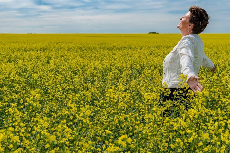 Posição caucasiano nova da mulher com os braços aumentados em um campo do canola imagem de stock