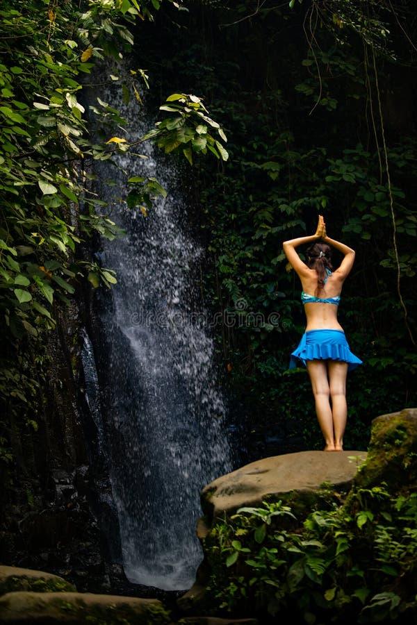 Posição caucasiano nova da mulher em de pedra, meditando, ioga praticando na cachoeira em Ubud, Bali, Indonésia imagens de stock