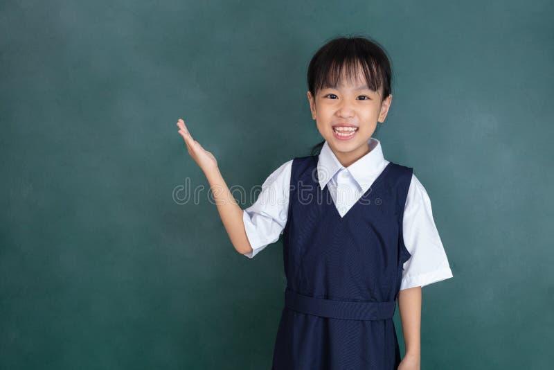 Posição chinesa asiática da menina na frente do quadro-negro verde foto de stock