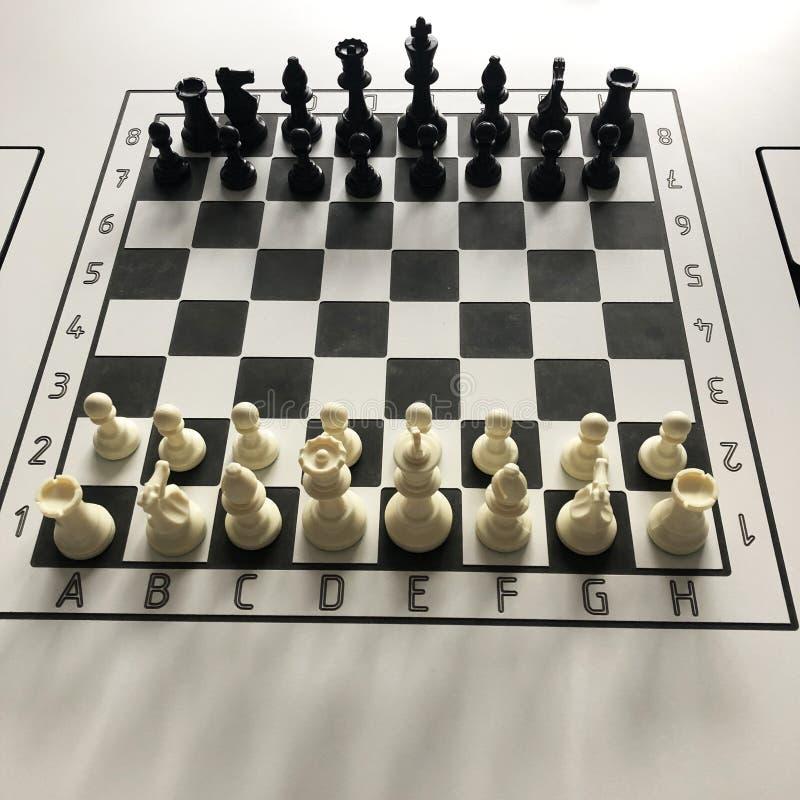 Posi??o come?ar sobre a xadrez da placa de esbo?os 8x8 na tabela fotografia de stock