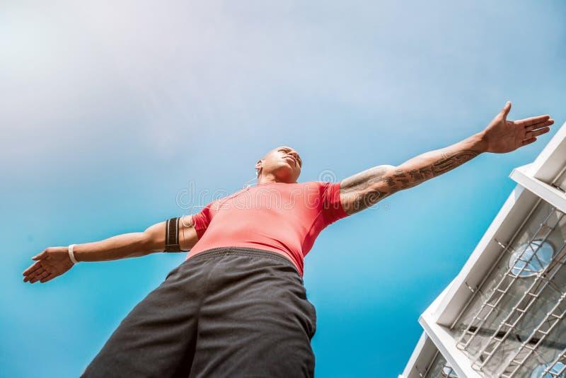 Posição considerável agradável do homem contra o céu fotografia de stock