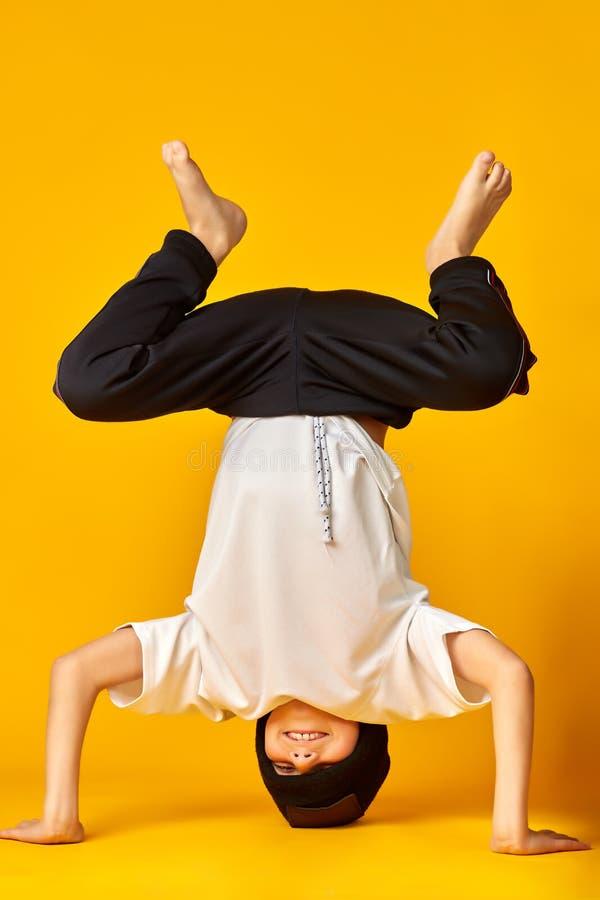 Posição considerável do dançarino da ruptura em sua cabeça no estúdio sobre o fundo amarelo foto de stock royalty free