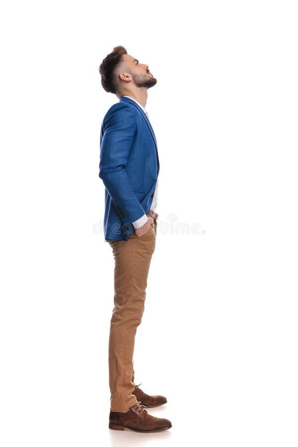 Posição considerável do homem com mãos em uns bolsos ao olhar acima fotos de stock royalty free