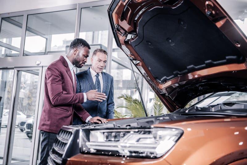 Posição considerável madura do homem de negócios perto do consultante antes de comprar o carro fotos de stock royalty free