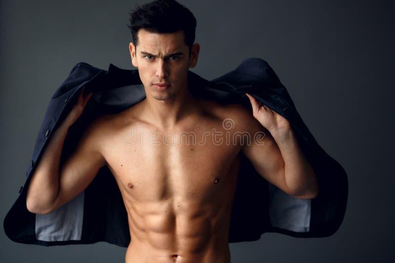 Posi??o consider?vel nova ? moda do homem e levantamento no terno elegante em um torso despido, isolado no fundo cinzento fotografia de stock