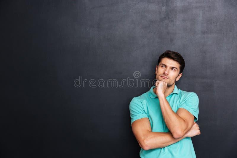 Posição considerável pensativa e pensamento do homem novo fotografia de stock royalty free