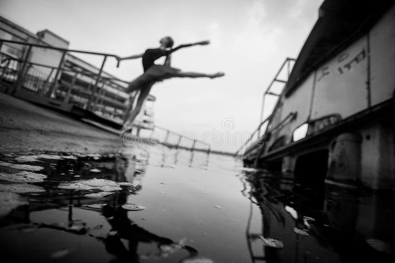 Posição da bailarina na pose do arabesque no fundo do rio, do cais e do barco velho imagens de stock royalty free