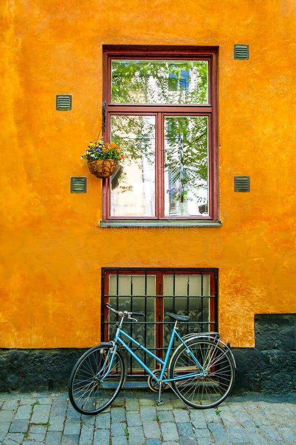 Posição da bicicleta do vintage dos azuis celestes na frente da parede de construção alaranjada vibrante da fachada com a janela  fotos de stock