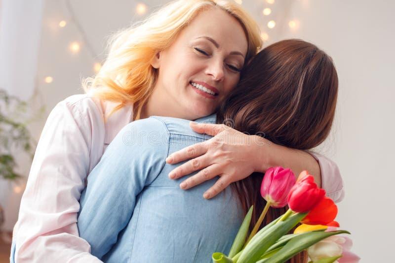 A posição da celebração da mãe e da filha junto em casa que abraça a mamã que guarda tulipas fechou os olhos fotografia de stock royalty free