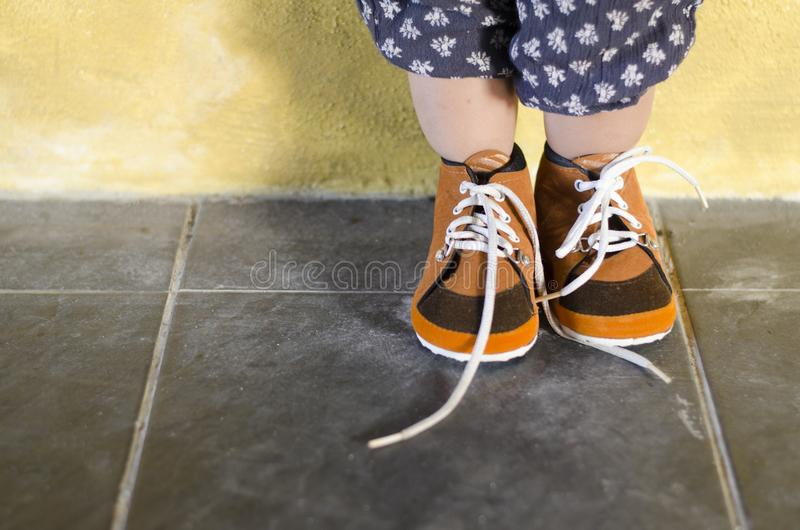 Posição da criança ao vestir sapatas marrons imagem de stock royalty free