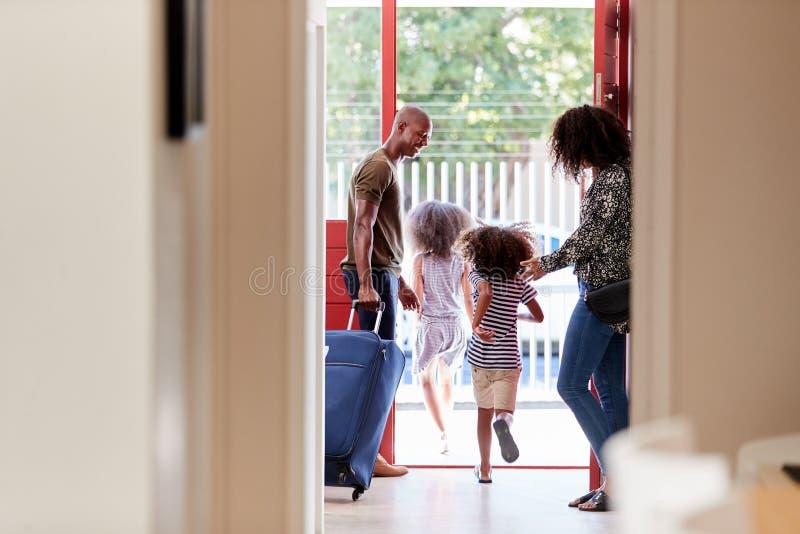Posição da família por Front Door With Suitcase About a sair para férias fotos de stock royalty free