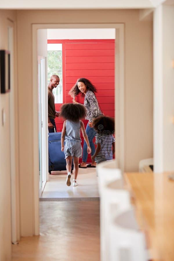 Posição da família por Front Door With Suitcase About a sair para férias fotos de stock