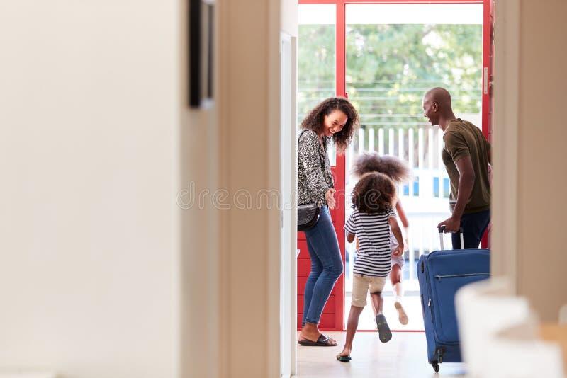 Posição da família por Front Door With Suitcase About a sair para férias imagem de stock