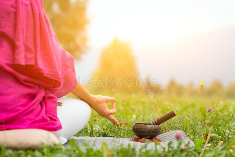 Posição da ioga com sino tibetano foto de stock