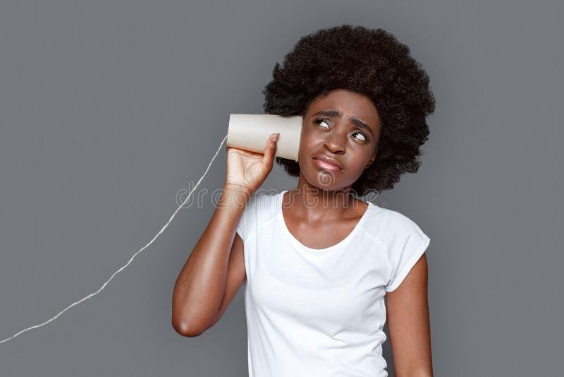 Posição da jovem mulher isolada no telefone de escuta cinzento do papel da conversação insatisfeito fotografia de stock