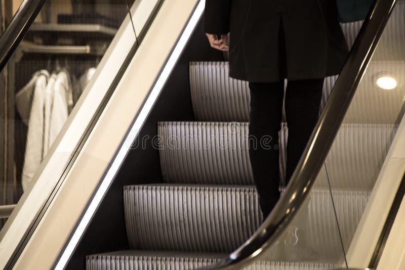Posição da jovem mulher na escada rolante em uma loja imagens de stock royalty free