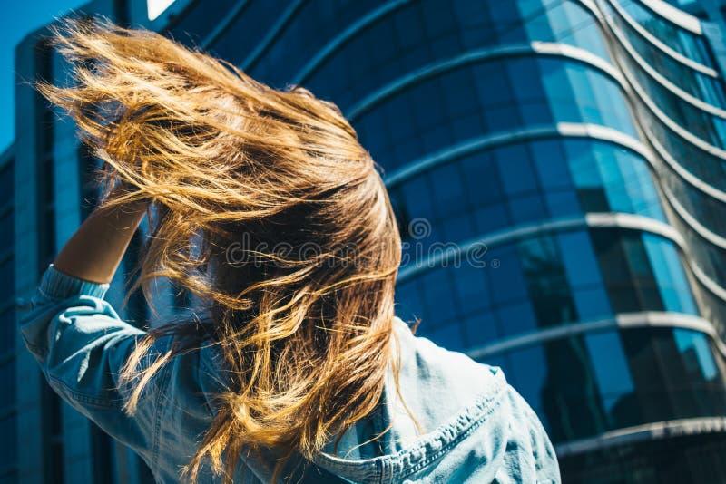 Posição da jovem mulher na frente da construção azul fotos de stock