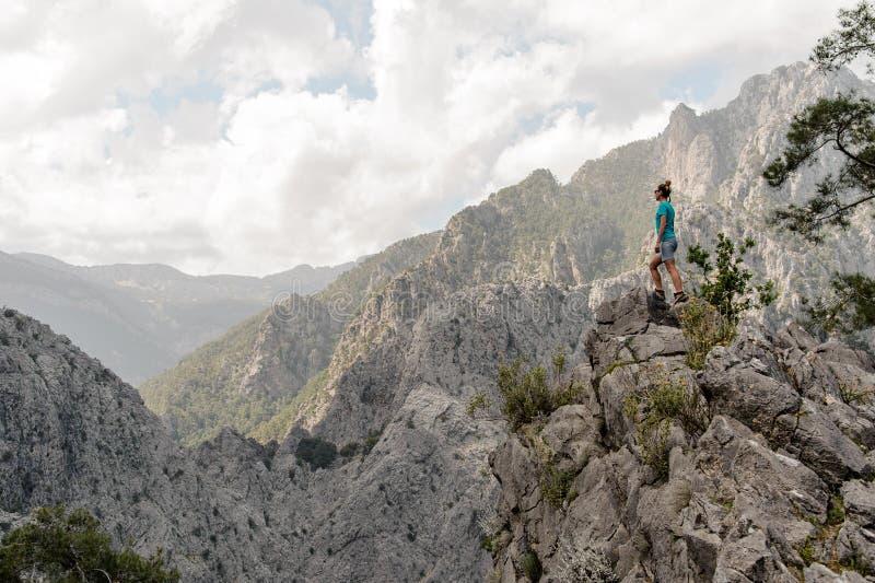 Posição da jovem mulher no auge da montanha imagens de stock
